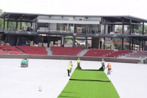 Employees of Sprinturf install the first roll of synthetic turf at Kokomo Municipal Stadium. Photo by Dean Hockney.