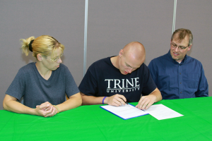 Eastern graduate Brent Bachman signs a letter of intent to play football at Trine University. (Photo by Dean Hockney)